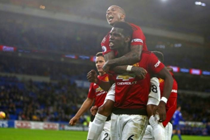 Les milieux de Manchester United Paul Pogba (bas) et Ashley Young (sur son dos) exultent après un but inscrit par Jesse Lingard sur le terrain de Cardiff, le 22 décembre 2018 Photo Geoff CADDICK. AFP