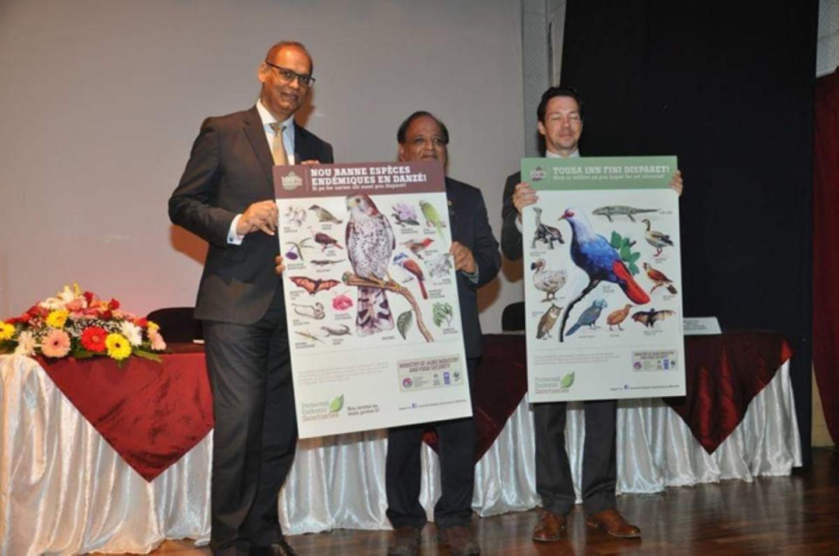 Le ministre de l'Agro-industrie, Mahen Seeruttun, tenant une pancarte énumérant les espèces protégées, dont notre chauve-souris.